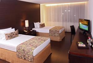 A bed or beds in a room at Hotel Estelar Milla De Oro