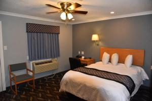 A bed or beds in a room at Purple Sage Motel