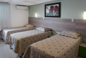 A bed or beds in a room at Pousada Florenza