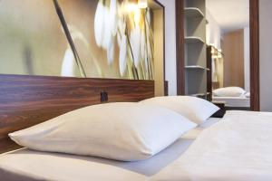 A bed or beds in a room at AZIMUT Hotel Cologne