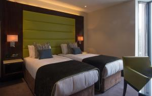A bed or beds in a room at St George's Hotel - Wembley