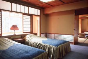 Кровать или кровати в номере Yunokaze HAZU