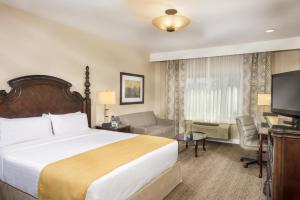 A bed or beds in a room at Ayres Suites Ontario at the Mills Mall