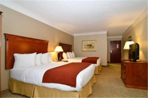 A bed or beds in a room at Baymont by Wyndham Madisonville