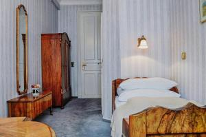 A bed or beds in a room at Garni Hotel Drei Lilien