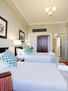 A bed or beds in a room at Albany Hotel