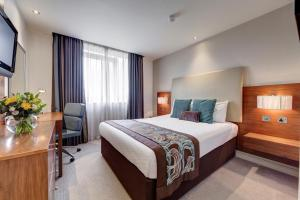A bed or beds in a room at Thistle London Hyde Park Kensington Gardens