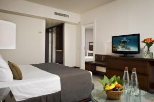 A television and/or entertainment center at Isrotel King Solomon Hotel