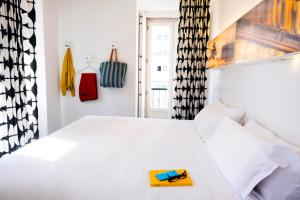A bed or beds in a room at Hotel Gat Rossio