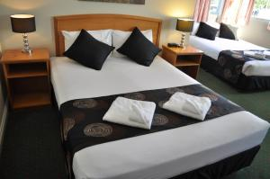 A bed or beds in a room at Meadowbrook Hotel Brisbane