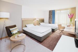 A bed or beds in a room at Mövenpick Hotel Zürich-Regensdorf