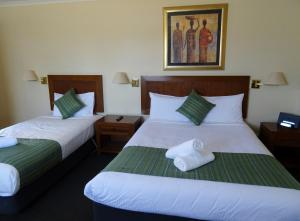A bed or beds in a room at Armidale Pines Motel