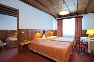 A bed or beds in a room at La Petite Chaumiere