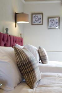 A bed or beds in a room at The Broadoak Hotel