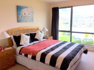 A bed or beds in a room at Alpine Suites Queenstown