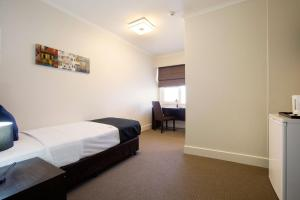 A bed or beds in a room at Enfield Hotel