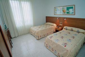 A bed or beds in a room at Hostal Virginia