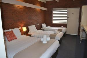 A bed or beds in a room at Wattle Motel
