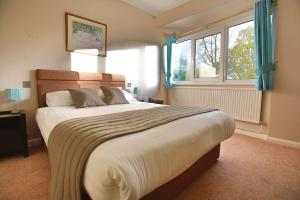 A bed or beds in a room at Best Western Plus Oaklands Hotel
