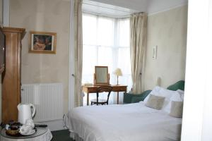 A bed or beds in a room at Holmwood House Guest Accommodation