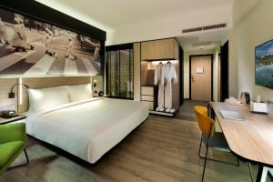 A bed or beds in a room at The Kuala Lumpur Journal Hotel