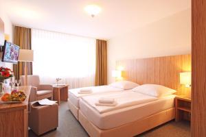 Ein Bett oder Betten in einem Zimmer der Unterkunft Akzent Hotel Am Burgholz