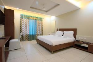 A bed or beds in a room at Hotel Sheela Shree Plaza