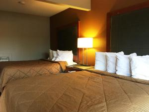 A bed or beds in a room at Chestnut Tree Inn Portland Mall 205