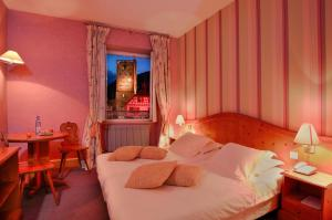 A bed or beds in a room at Hôtel De La Tour