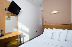 A bed or beds in a room at Eden Plaza Kensington