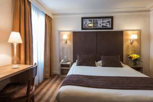 A bed or beds in a room at Hôtel Vivienne