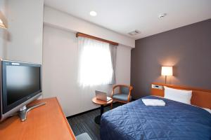 A bed or beds in a room at Hotel Unisite Sendai