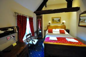 A bed or beds in a room at The Greyhound Coaching Inn