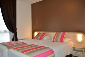 A bed or beds in a room at Brit Hotel Cherbourg
