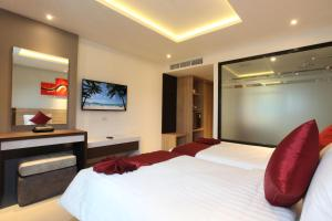 A bed or beds in a room at Paripas Patong Resort