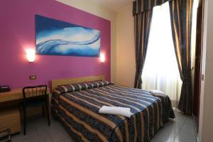 Un pat sau paturi într-o cameră la Hotel Loreto