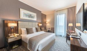 A bed or beds in a room at Hawthorn Suites by Wyndham Abu Dhabi City Center