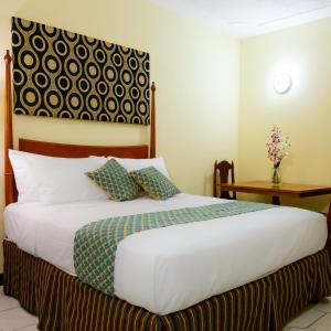 A bed or beds in a room at Jasmine Inn