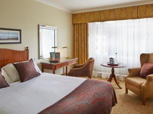 A bed or beds in a room at Macdonald Berystede Hotel & Spa
