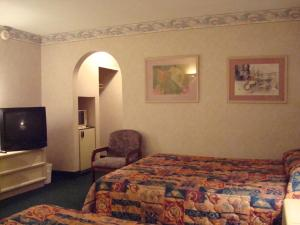 A bed or beds in a room at O'Hare Inn & Suites