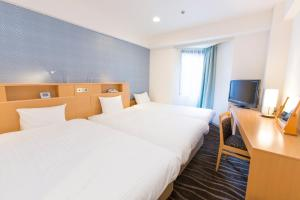A bed or beds in a room at Shibuya Tobu Hotel