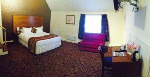 A bed or beds in a room at The Three Tuns Hotel Wetherspoon