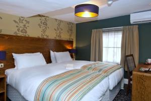 A bed or beds in a room at The Hatchet Inn Wetherspoon
