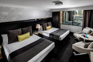 A bed or beds in a room at Pullman Brisbane King George Square