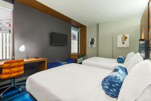 A bed or beds in a room at Aloft Greenville Downtown