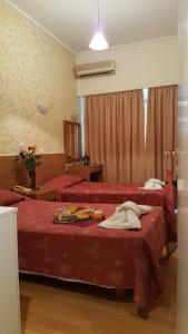 A bed or beds in a room at Aristoteles Hotel