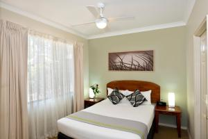 A bed or beds in a room at Leisure Inn Pokolbin Hill