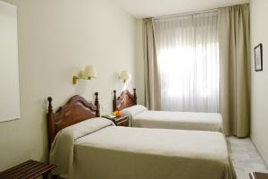 A bed or beds in a room at Hotel San Pablo Sevilla