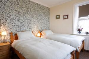 A bed or beds in a room at Arkleside Country Guest House