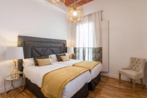 A bed or beds in a room at Bibo Suites Oro del Darro
